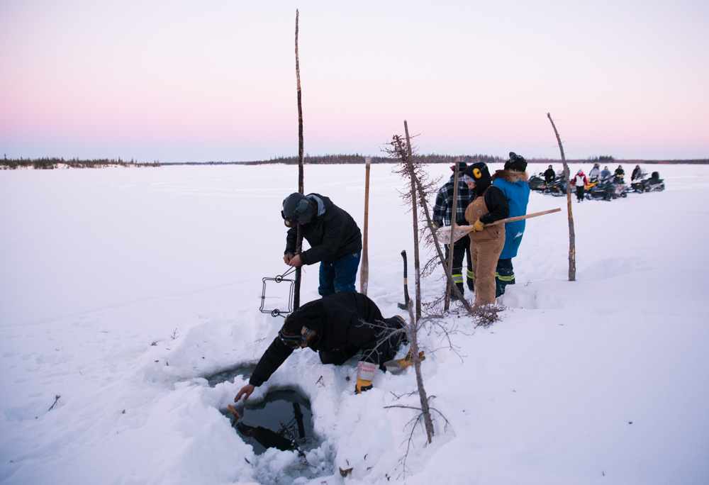 Trappers from Fort Good Hope, Northwest Territories, check a trap during a winter harvest. In recent years, the remote community has dealt with a vicious murder and sucide among its youth. To help cope, leaders and elders encourage residents to go back on the land as a community to relearn their traditions and heal together by working outside with each other.