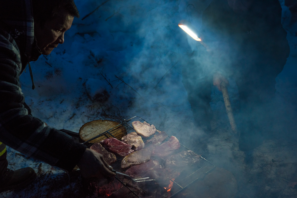 Floyd Kakfwi seasons fish and steaks on a campfire. After a long day of hunting, dinner is finally prepared.