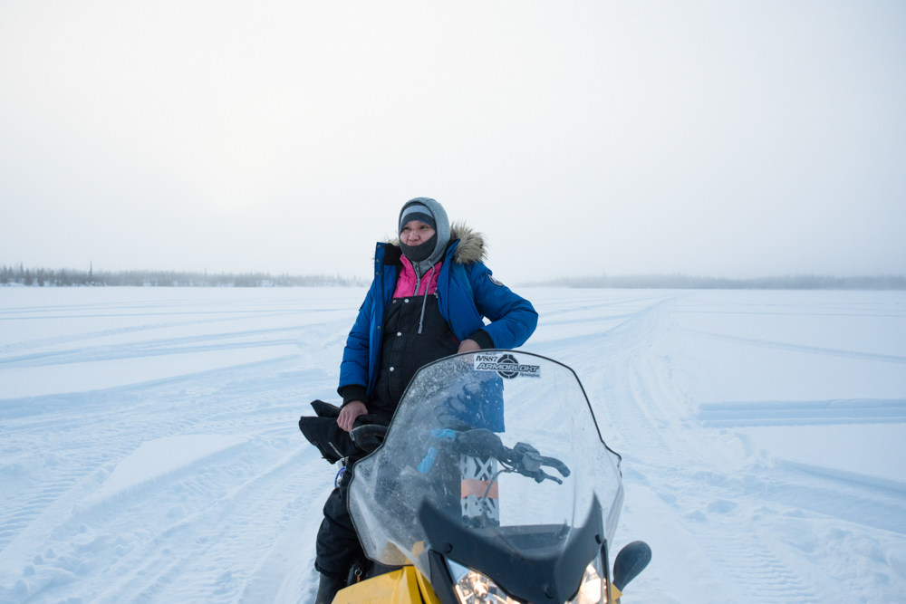 Lois Rabesca takes a break on a ski-do while scouting for moose and caribou in the Ts'udé Nilįné Tueyata protected area near Fort Good Hope, Northwest Territories.