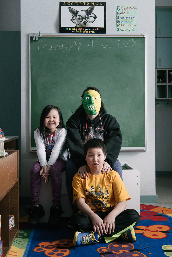 """LA poses with her two younger siblings in the classroom. For LA, who often takes care of her brothers and sisters, a sense of responsibility to them keeps her mind clear. """"If I was gone, who would watch out for them?"""" April 11, 2018, Gambell, AK."""