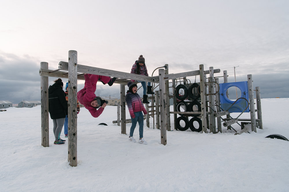Kids play on a snowy playground in the light of Arctic spring. With each new generation, traumas of previous generations grow more distant, though they will face new challenges.