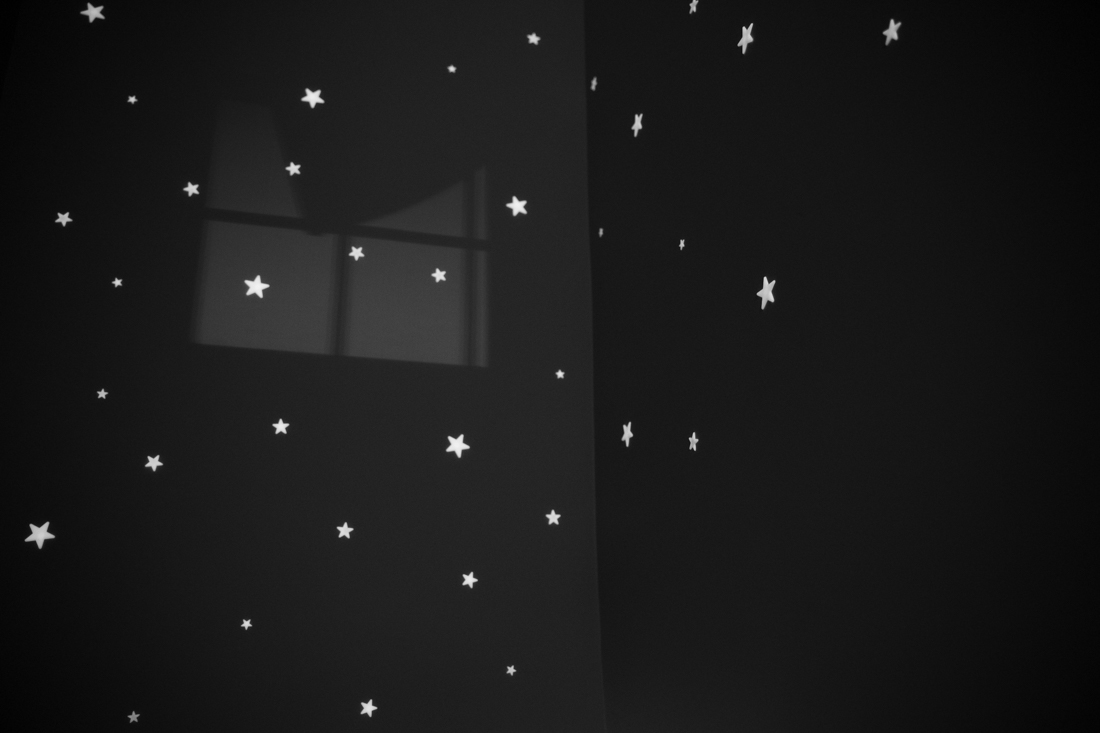 The silhoutte of a nearby window shines above the glowing plastic stars that decorate the Hickey's stairwell.Arlington, MA. May 1, 2020. Life has continued on for the Hickey family through the uncertainty of a global pandemic, life is still strange and continues changing, but the family looks back on the strange circumstances of their reunion in quarantine as an unexpected opportunity to spend time with those we love most.