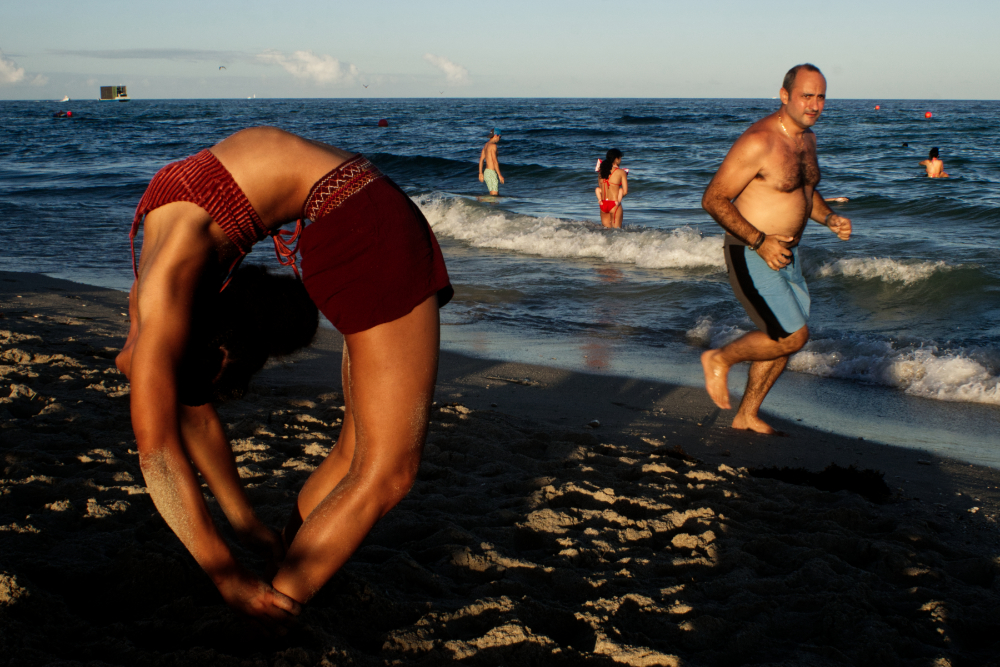 Dereka Nawracay, left, completes a full back bending pose as a man runs along the edge of the ocean in South Beach on November 15, 2020.