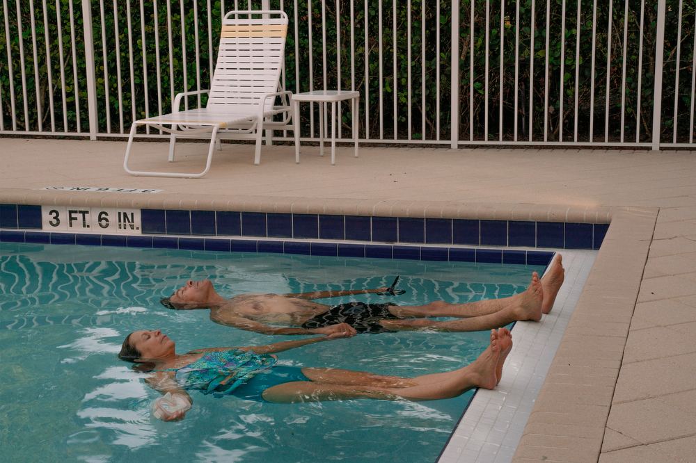 A woman named Diana and her husband lay in a community pool in Jupiter, Fla. on Aug. 11, 2020. They exercise like this holding hands during a time when gyms were closed due to the coronavirus pandemic.
