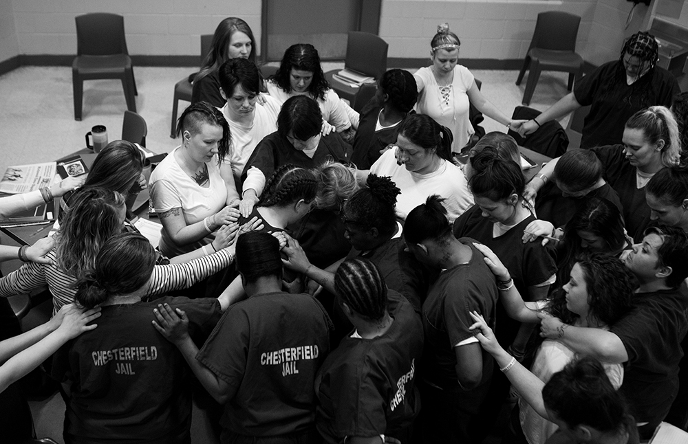 """Women of the Heroin Addiction Recovery Program at the Chesterfield County Jail outside of Richmond, Va. """"pray out"""" a participant as she is released from jail."""