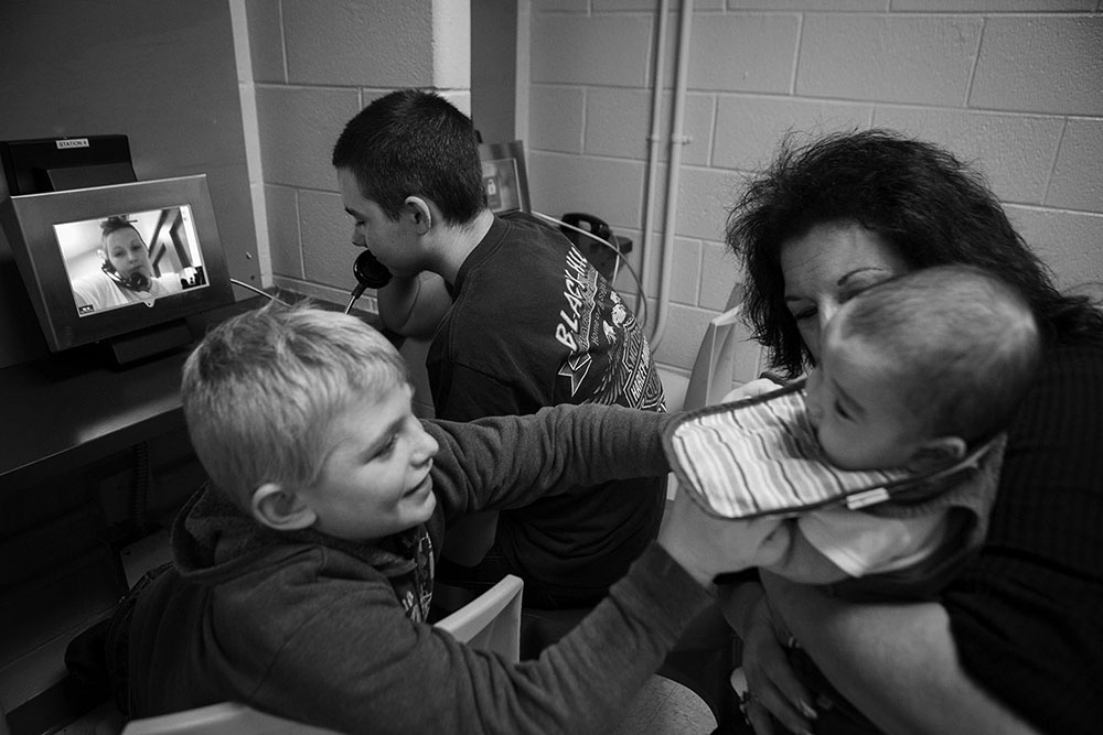 """Jeremy talks with his mother Tera Crowder while James plays with Jaydon in his grandmother Deborah Crowder's arms during a video visit with their mother, Tera, at the Chesterfield County Jail. Tera's four children are: 16-year-old twins Jeremy and Jacob, seven-year-old James and three-month-old Jaydian. """"You're lucky with the twins. Jacob takes it a little harder ... they don't say nothing bad about you. They just don't expect much,"""" Deborah said to her daughter during the visit."""