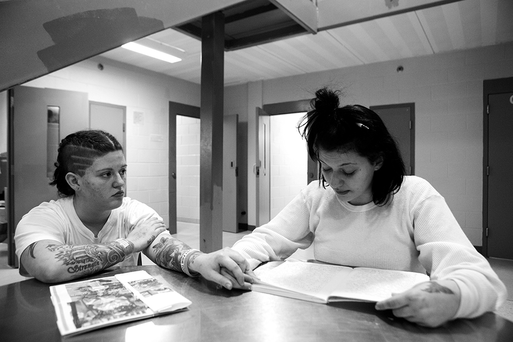 """Michelle Blanely (left) holds Stephanie Crowder's hand while she reads an """"Impact letter,"""" a letter written to herself from the perspective of her five-year-old son. """"I'm scared for you Stephanie. There are fuckers out there who are going to give it [heroin] to you for free,"""" Michelle said while Stephanie talked about her impending release."""