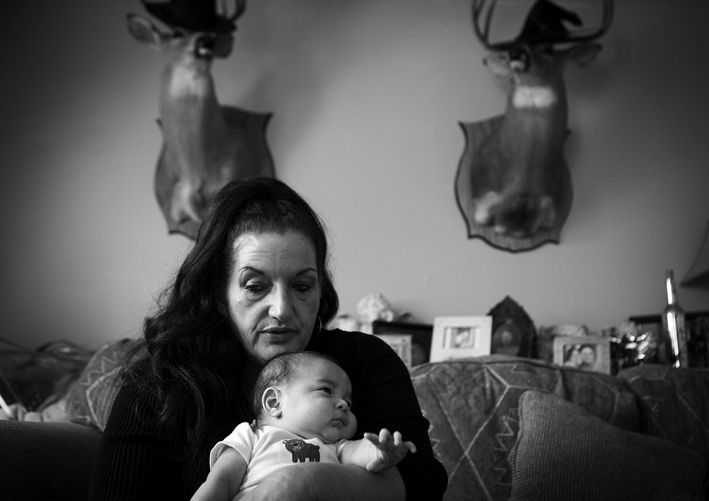 Deborah Crowder, 54, holds her youngest grandson, Jaydian, three-months, at a friend's house in early November. Deborah has custody of her oldest daughter, Tera's four children. Jaydon was born while Tera was in jail. She held him for two days before turning him over to the nurses who turned him over to her mother.