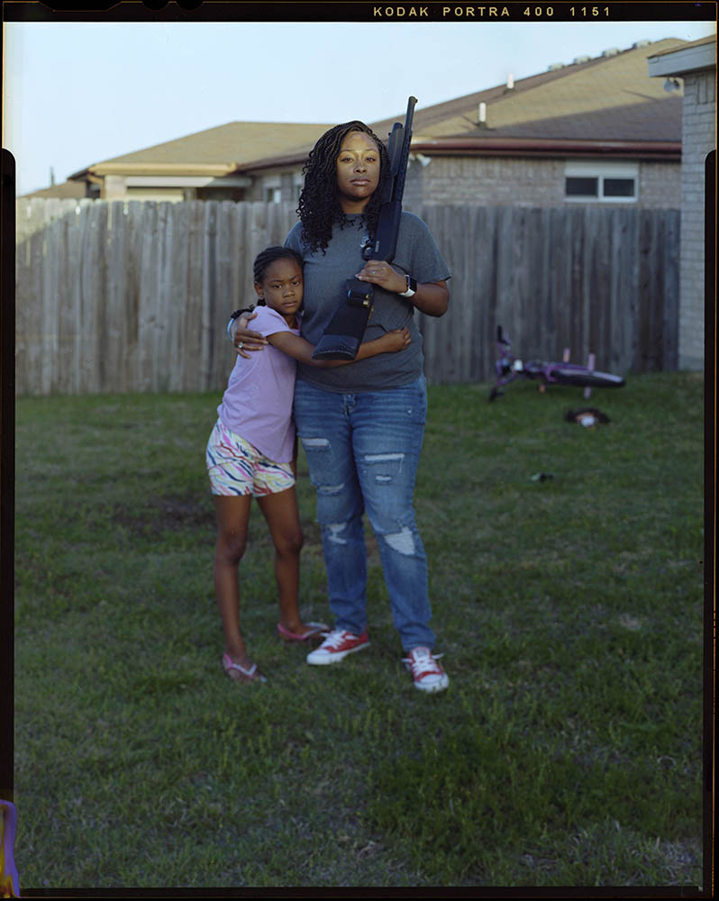 """Damillah Lane, 26, is embraced by her daughter Skylar Lane, 8, as she holds her firearm outside of her home on Saturday, April 10, 2021 in Killeen, Tx. """"Whenever my husband leaves I feel a need to protect my family,"""" Damillah said."""