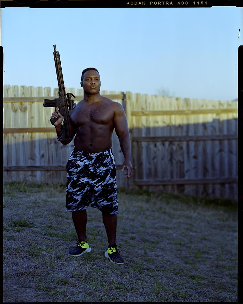 """Ron Harris, 32, postures his firearm in his backyard on Tuesday, March 2, 2021 in Killeen, Tx. """"I own it to protect my family because I cant afford a loss,"""" Harris said."""