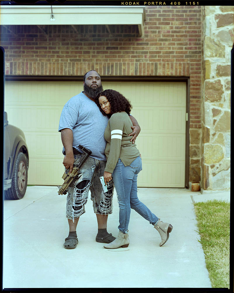 """Tylissa Frazier, 38, right, is embraced by her husband Kenneth Frazier, 35, outside of their home as they hold their fireamrs on Saturday, April 3, 2021 in Temple, Tx.  """"We get pulled over a lot so having a license will show that we are law abiding citizens,"""" Tylissa said."""