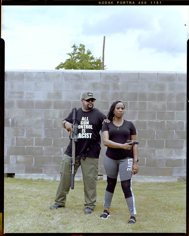 """Trina' Duncan, 39, foreground, postures her pistol outside a local gun range after training with her pastor Andrew Long, 46, on Saturday, May 16, 2021 in Killeen, Tx. According to the Pew Research Center Women are less likely to own a firearm compared to Men. """"I have been in moments that would not have occurred if I was a guy,"""" Duncan said."""