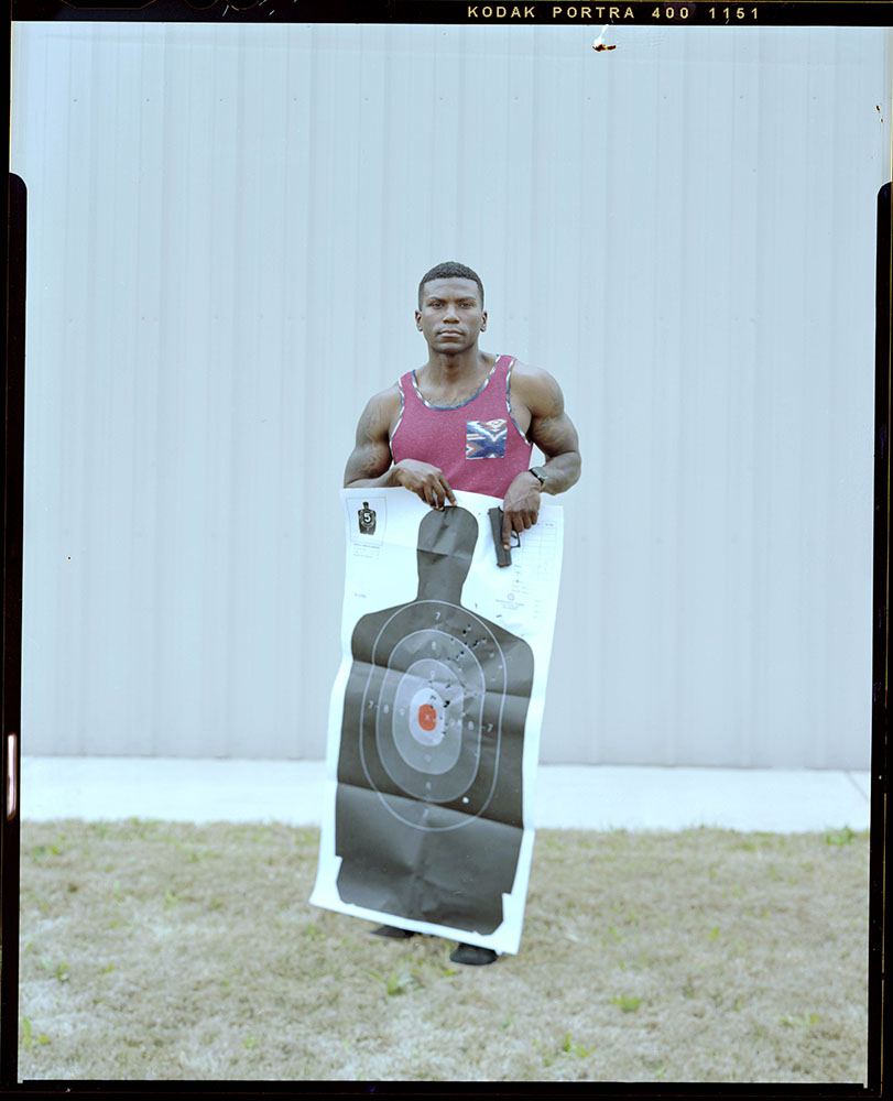 """Lindberg Wilborn, 32, stands holding the target he used to qualify for his license to carry outside a local gun range on Saturday, March 27, 2021 in Killeen, TX. He has owned his firearm for about 3 months. """"Society looks at black men as predators and scary people so most of us are scared to own a firearm in fear of fueling the fear that already exists,"""" Wilborn said."""