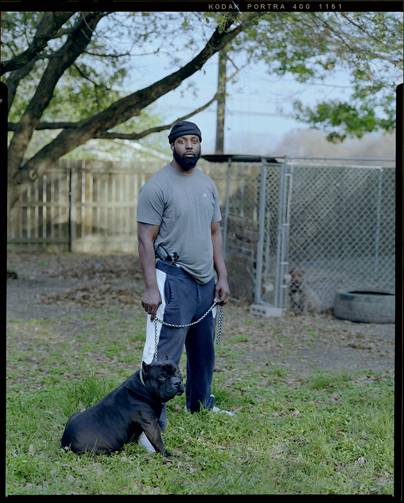 """Marvin West, 39, holds his dog outside of his home with his firearm positioned on his hip on Monday, April 06, 2021 in Killeen, Tx. """"It's more to the picture than what you see,"""" West said. People often judge him based on his appearance. He mentions that those people would be surprised to know that he's an educated business owner that holds a Masters degree."""