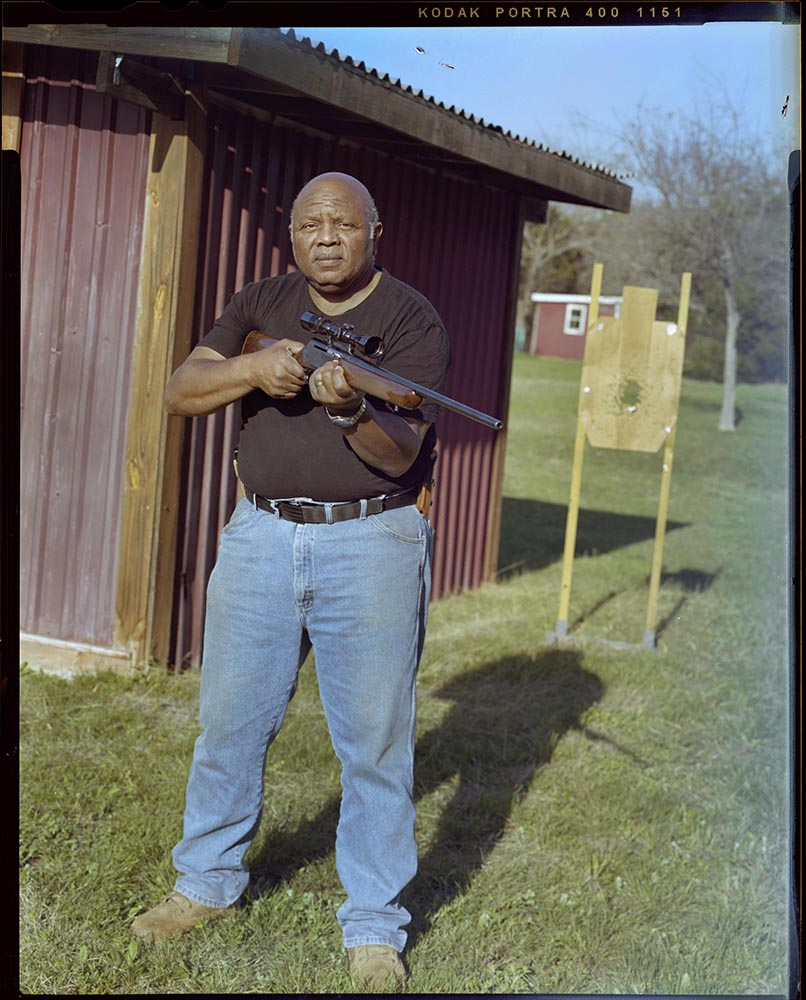 """William Wilson, 64, postures his rifle near a gun range in his friends backyard on Sunday, March 21, 2021 in Copperas Cove, Tx. Wilson has over 45 years of gun experiance. He spent 21 years in the military, 22 years as a police officer and currently serves as a sales clerk at a local gun store. """"The problem with big city policing is that a black man with a gun ia a threat, they'll probably shoot me before they find out im a retired police officer,"""" Wilson said."""