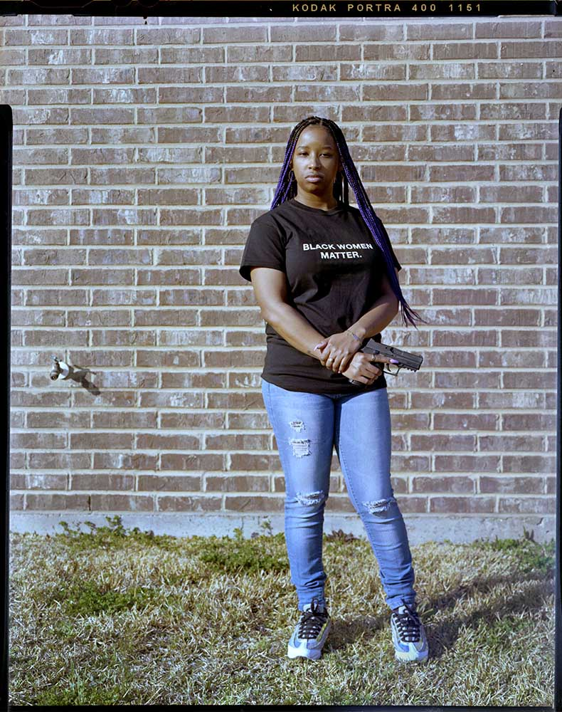 """Brittney Saunders, 28, holds her firearms outside of her home on Friday, March, 05, 2021 in Killeen, Tx. """"Why can other races have assaut rifles and machine guns but if black people have a handgun we are considered a threat,"""" Saunders said."""
