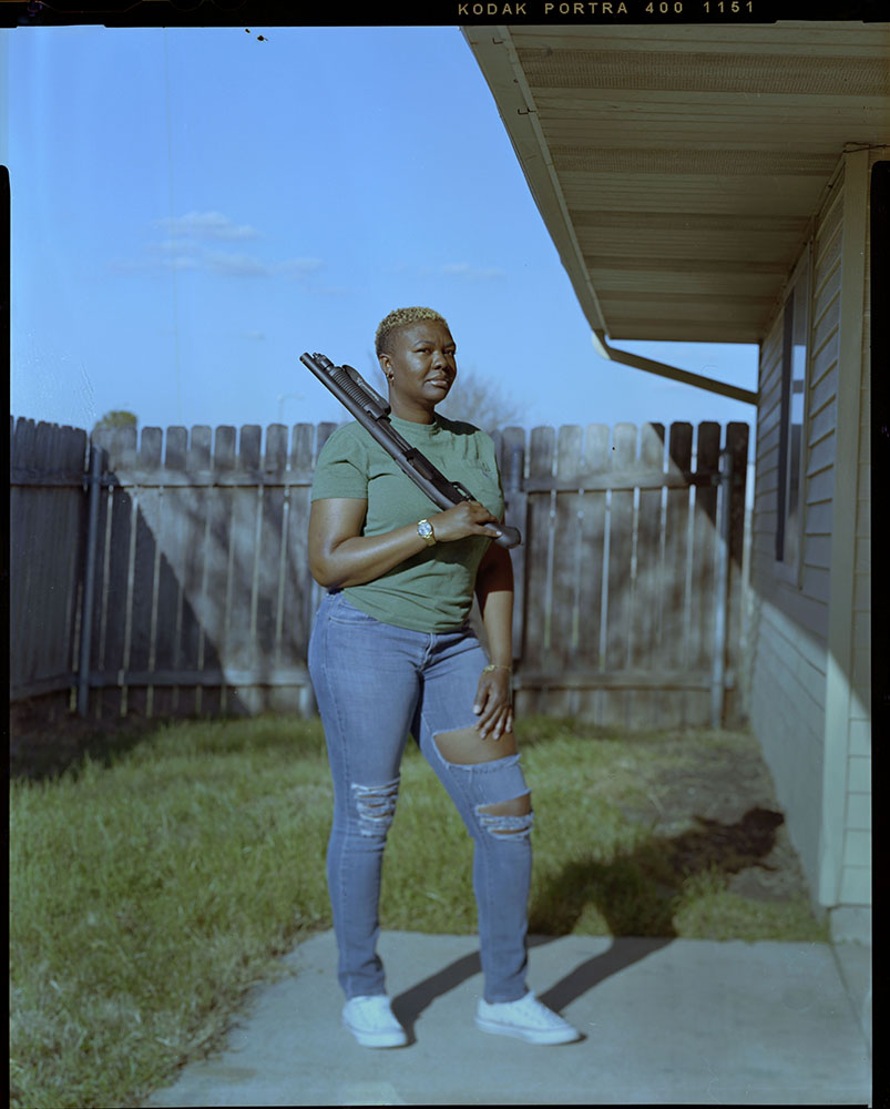 """Asia Wragg, 35, holds her firearm outside of her home on Wednesday, March 10, 2021 in Fort Hood, Tx.  """"As a single woman with children my priority is to protect and defend my family,"""" Wragg said."""