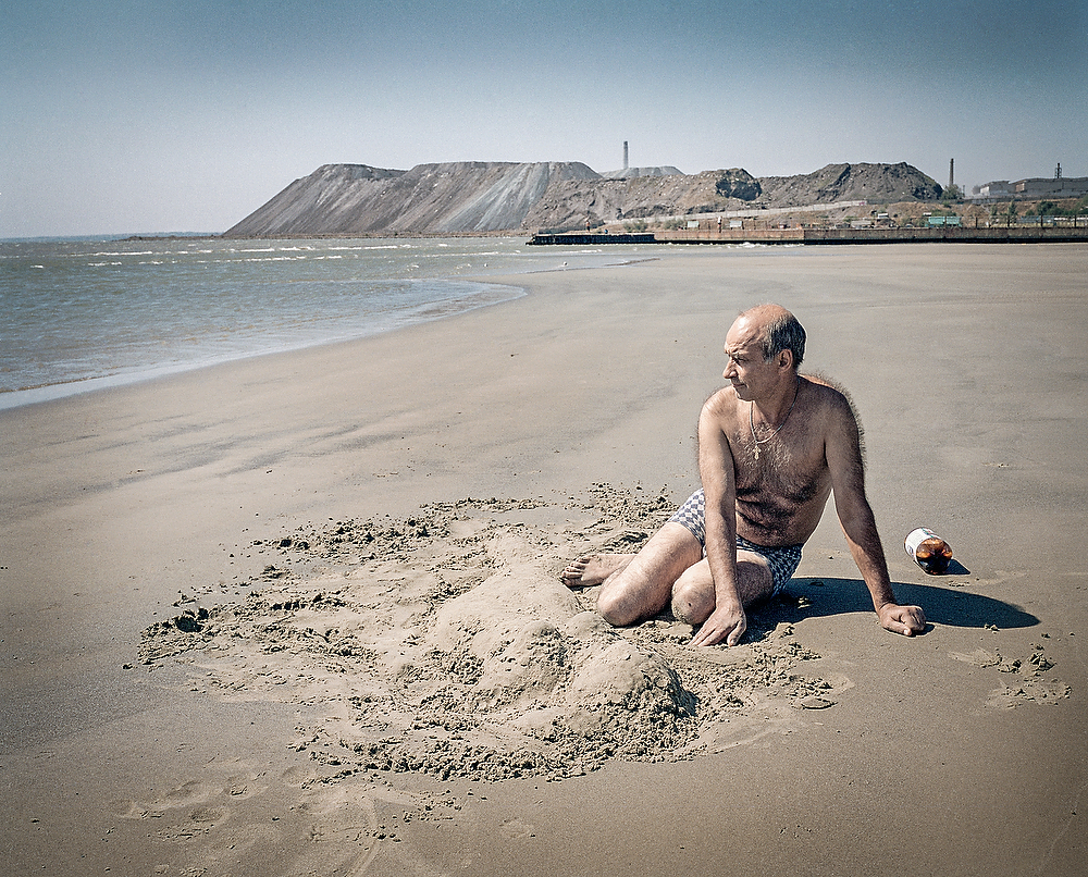 September 2014, Mariupol , Ukraine  Valera Starikov (39 ) makes a sand mermaid on the beach in Mariupol city where he  fled the war together with his wife  .  His village was under rebel control and  place of his work was under Ukrainian  control. Valera did not want to loose his work  so each day he bicycled across the frontline between Avdiivka and Yasynivka .  After he was caught at the cross fire few times he fled. I   become  grey from stress -he told me pointing at his hair.