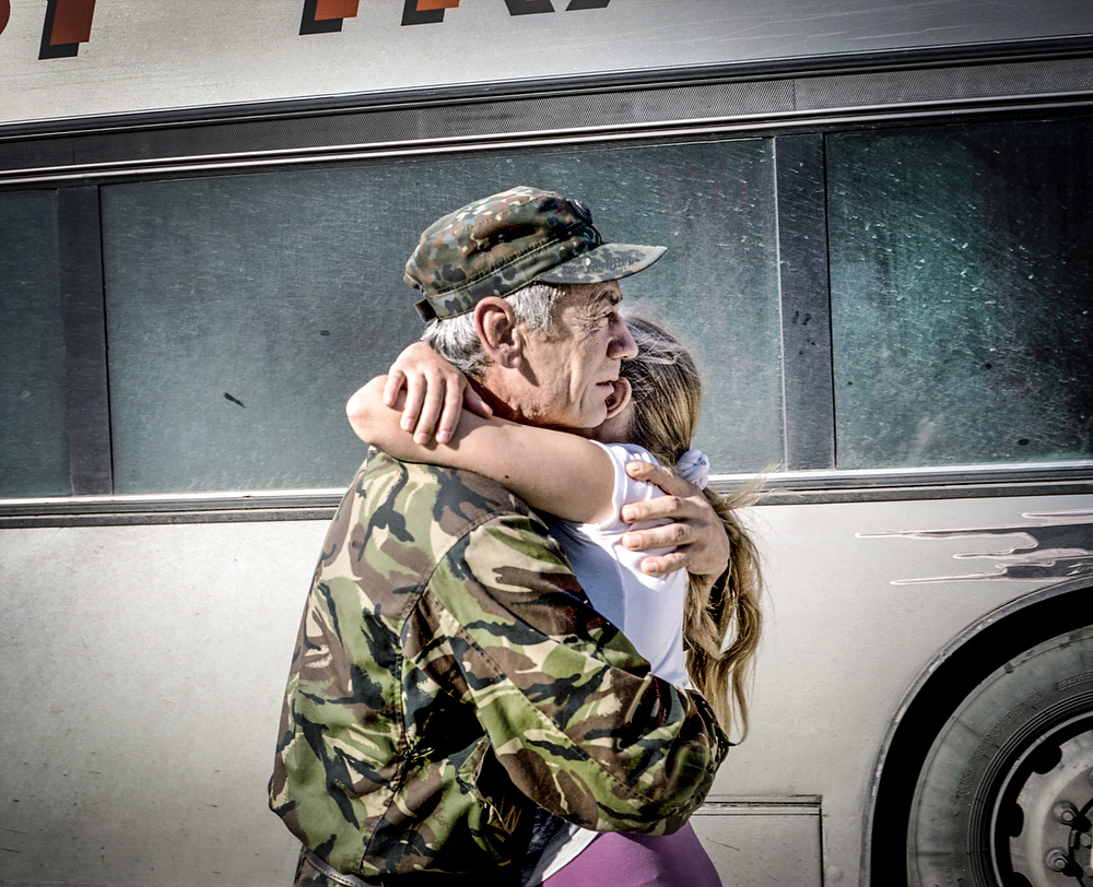"""July 2015 , Cherkasy Captain Kasyanenko Nikolay Vasilevich holds his daughter after arriving  from the front line back home , where he was for a year.  When the war started he was retired from the army but immediately went to sign up as a volunteer to fight . After serving year on the front line he continues to work in the army in his region : """"As long as the war will continue I will serve, and what will bring tomorrow only God Decides """" he told me in December 2015."""