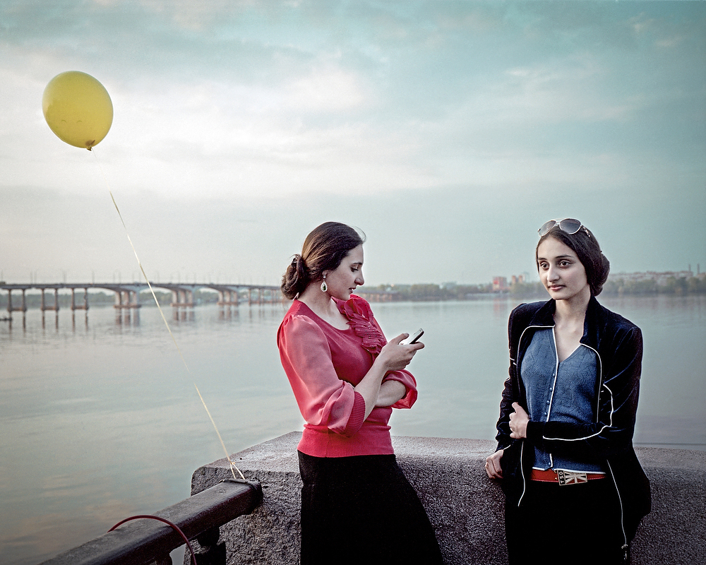 April 2014 , Dniepropetrovsk  Two Roma Sisters Ruslana ( 16  ) and Milana (19 ) taking the evening stroll along the Dnieper River.  I came there from Donetsk and Slavyansk where war was unfolding and armed rebels terrorized its residents. In  Dniepropetrovsk life was quiet ,  people stroll along the river as war not far away did not affect them directly.
