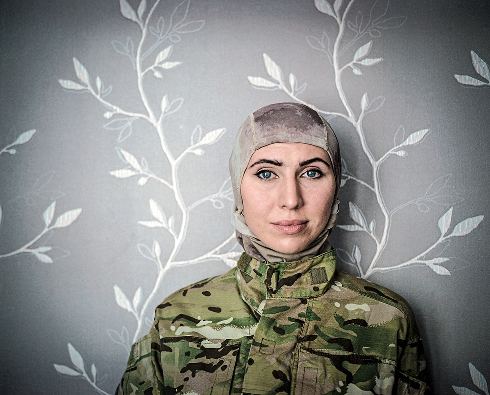 """July 2015, Odessa Amina Okuyeva doctor turned soldier poses for the photo in a flat she shares with her mother and son. Amina left war-torn Chechnia (II Chechen war )and moved to Odessa where she studied and become a doctor. She was on Maidan from December 2014 working as a medical volunteer. In that time her husband was in prison accused of the attempt to kill Russian President V. Putin. After Euromaidan revolution he was pardoned   and together with Amina joined """" international peacekeeping battalion"""" of volunteers to support Ukraine in fighting against the pro-Russian insurgency. Presently she is a fighter n the Brigade named after first Chechen president Dzhokhar Dudayev  . She also serves as a Brigade  Press officer."""