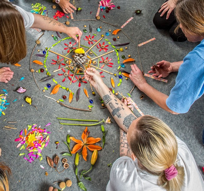 Creating a mandala with flower petals, at California Institution for Women. 2016