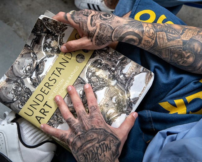 An art student holds a textbook, in a classroom at Calipatria State Prison. 2018