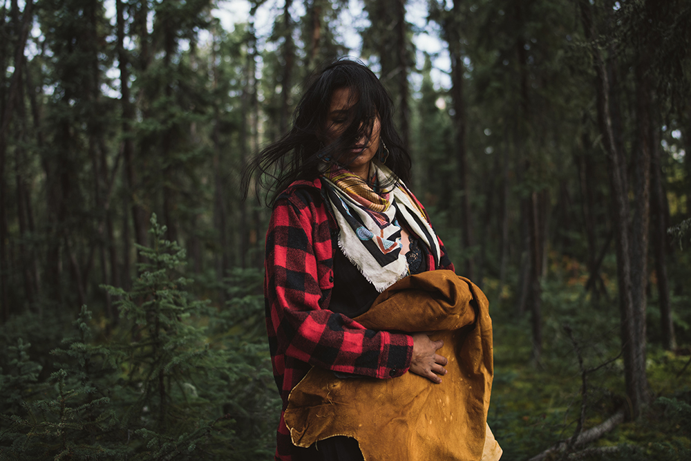 """Melaw Nakehk'o is a moosehide tanner, an artist, a filmmaker and mother. """"Through the process of reclaiming my cultural knowledge, I saw how the many teachings woven into our land practices could positively impact our first nation communities. Our Dene protocols and laws govern our reciprocal relationship with the land and animals. Moosehide tanning is a foundational Indigenous art form, it was our homes, our transportation, our clothes and in hard times our sustenance. It is the canvas of our visual cultural identity. The smoke smell triggers memories of grandmothers, the sound of scraping reminds us of our aunties working together, the beadwork and style of our moccasins represent our nations. Hide tanning is a revolutionary act of resistance. We occupy our traditional land, we are adhering to our traditional teachings and honoring our relationship with the animals that sustain us. Moosehide Tanning is Land Back""""."""