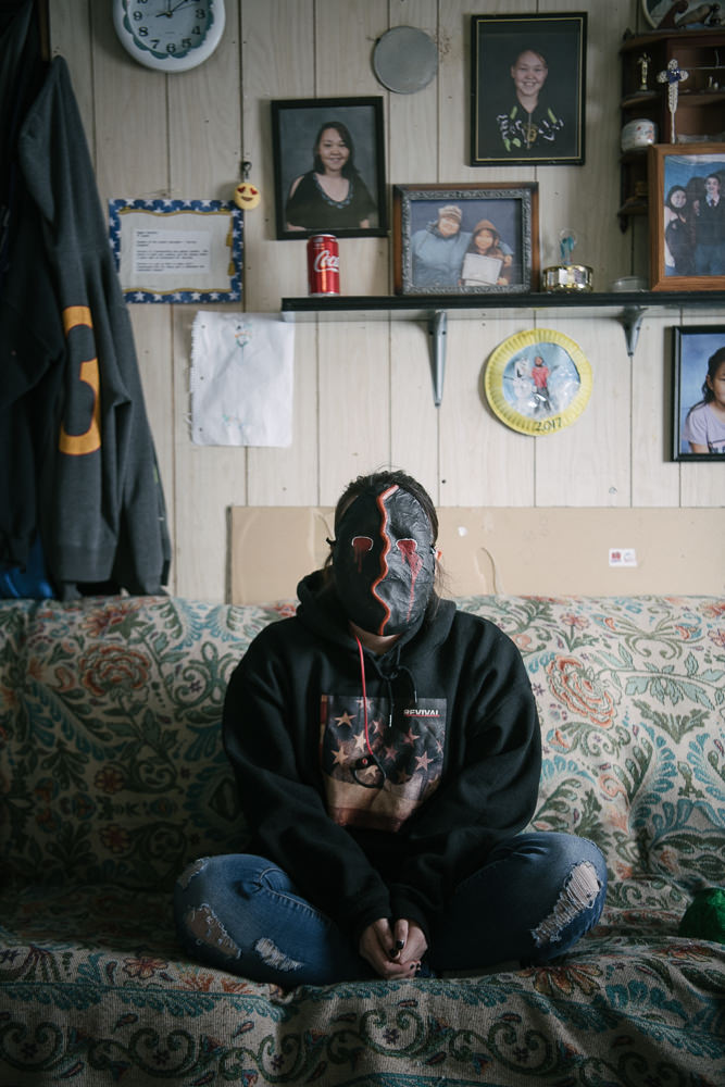 LA reflects on family and loss at home in her mask of grief. Though her family has more than most, she is not insulated from the near-constant stream of deaths in the community, from cancer to suicide. April 12, 2018, Gambell, AK.