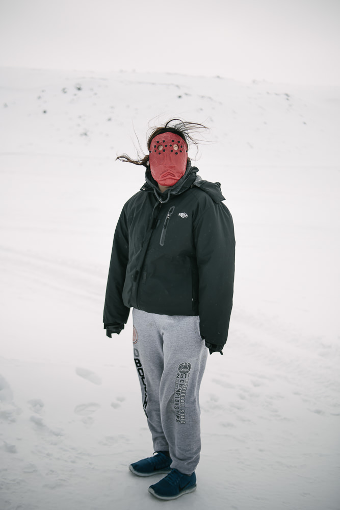 MB wears her mask of grief a few steps from family's front door. She lost her father to suicide last year, yet upon meeting in person, her resilience is evident in her energy and vibrance. April 12, 2018, Gambell, AK.