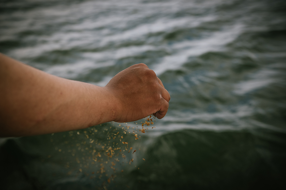 Chase Lockhart makes an offering of tobacco, a way to show respect to the water and pray for safe travels upon it.