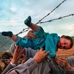 05/03/1999 - SLUG: FO/LIFE IN EXILE - THE CAMPS DATE: 5/3/99 - PHOTOG: Carol Guzy/The Washington Post  -  LOCATION: Kukes, Albania. CAPTION: LIFE IN EXILE - THE CAMPS:  Agim Shala, 2 years old, is passed thru the barbed wire fence at the Arab camp as members of the Shala family are reunited after fleeing Kosovo.  The relatives who just arrived from Prizren had to stay outside the camp until shelter was available.